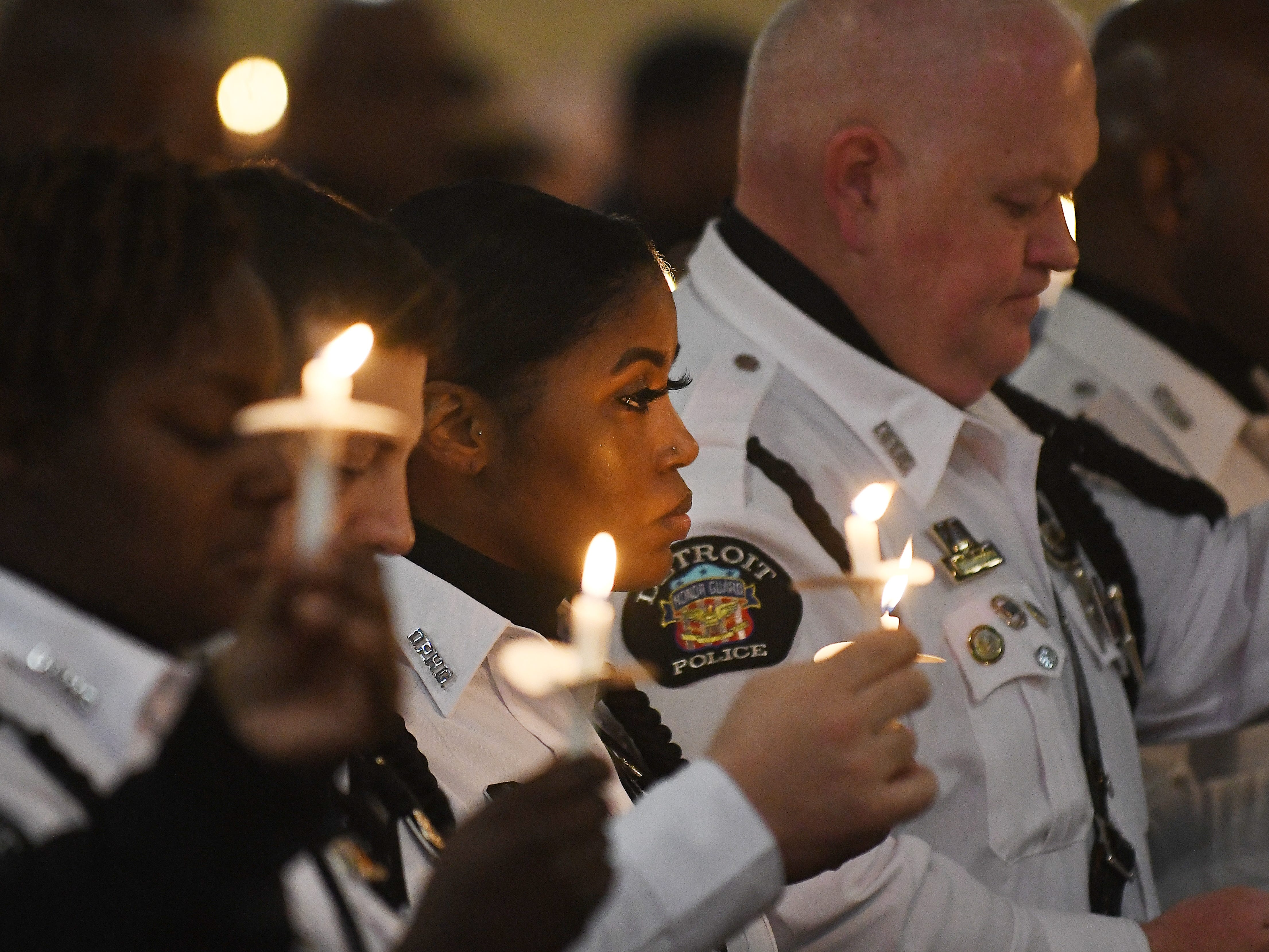 Officer Brittney Williams and members of the Detroit Police Honor Guard raise candles during the reading of the Memorial Roll Cal 2019 during the 46th Annual Detroit Police Interfaith Memorial Service and march to honor fallen officers at Old St. Mary's Church in Detroit, Michigan on May 3, 2019.