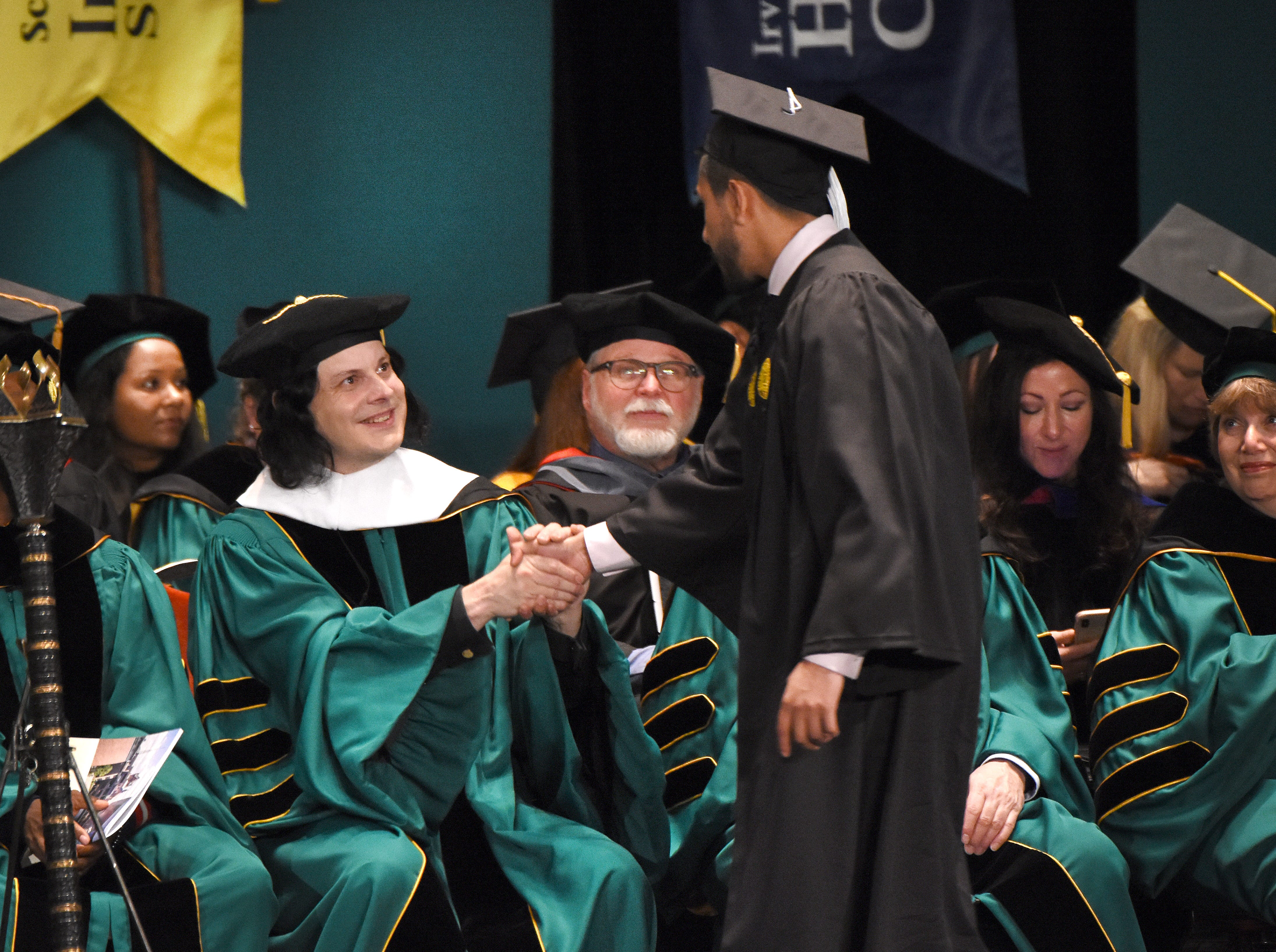 Musician Jack White shakes hands with graduates as they receive their degrees during Wayne State University commencement exercises at the Fox Theatre on Friday, May 3, 2019.