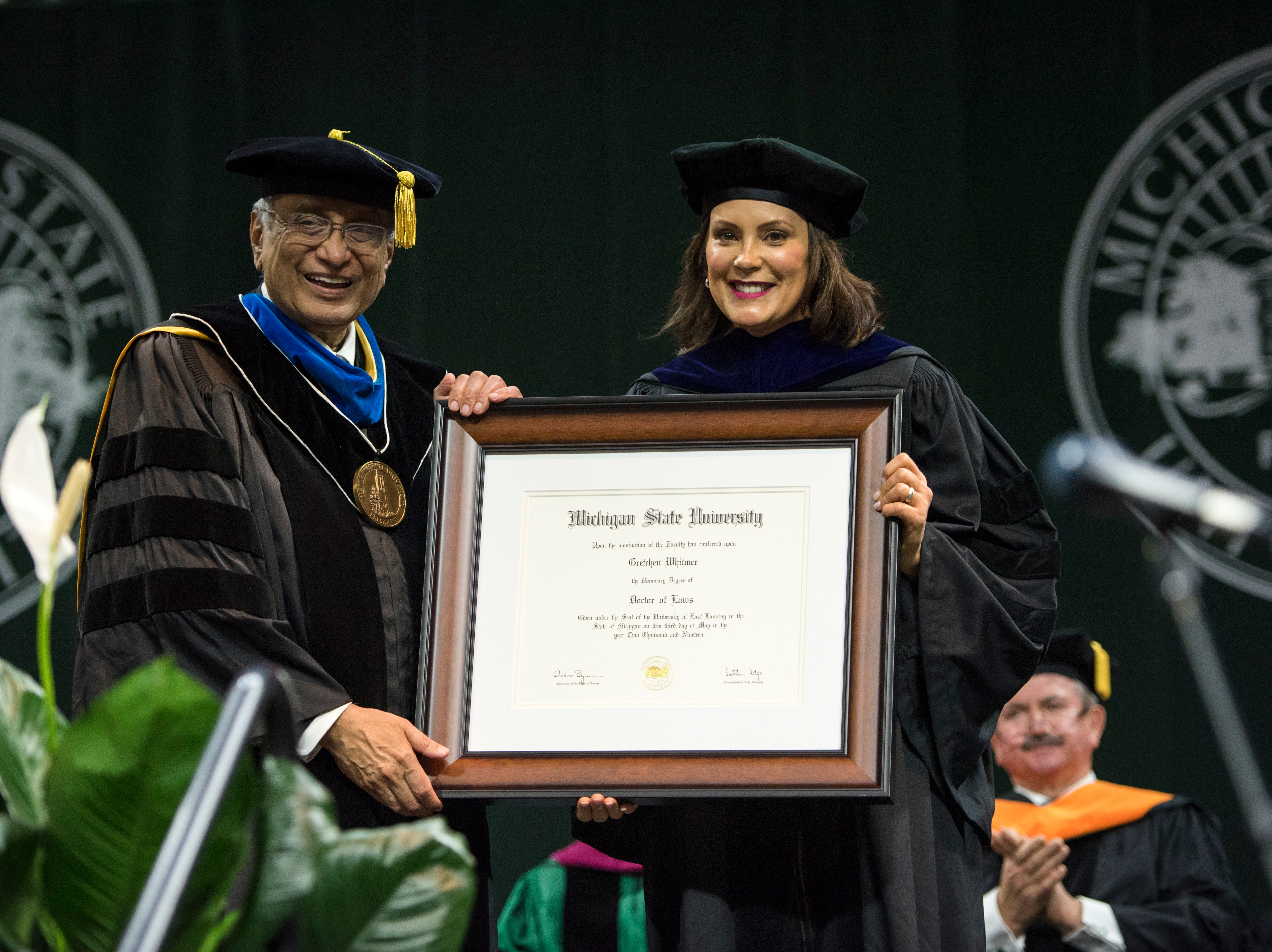 MSU Acting President Satish Udpa, left, and Michigan Gov. Gretchen Whitmer pose with Whitmer's honorary Doctor of Laws degree during the MSU Advanced Degrees Commencement ceremony at Breslin Center in East Lansing on Friday, May 3, 2019.