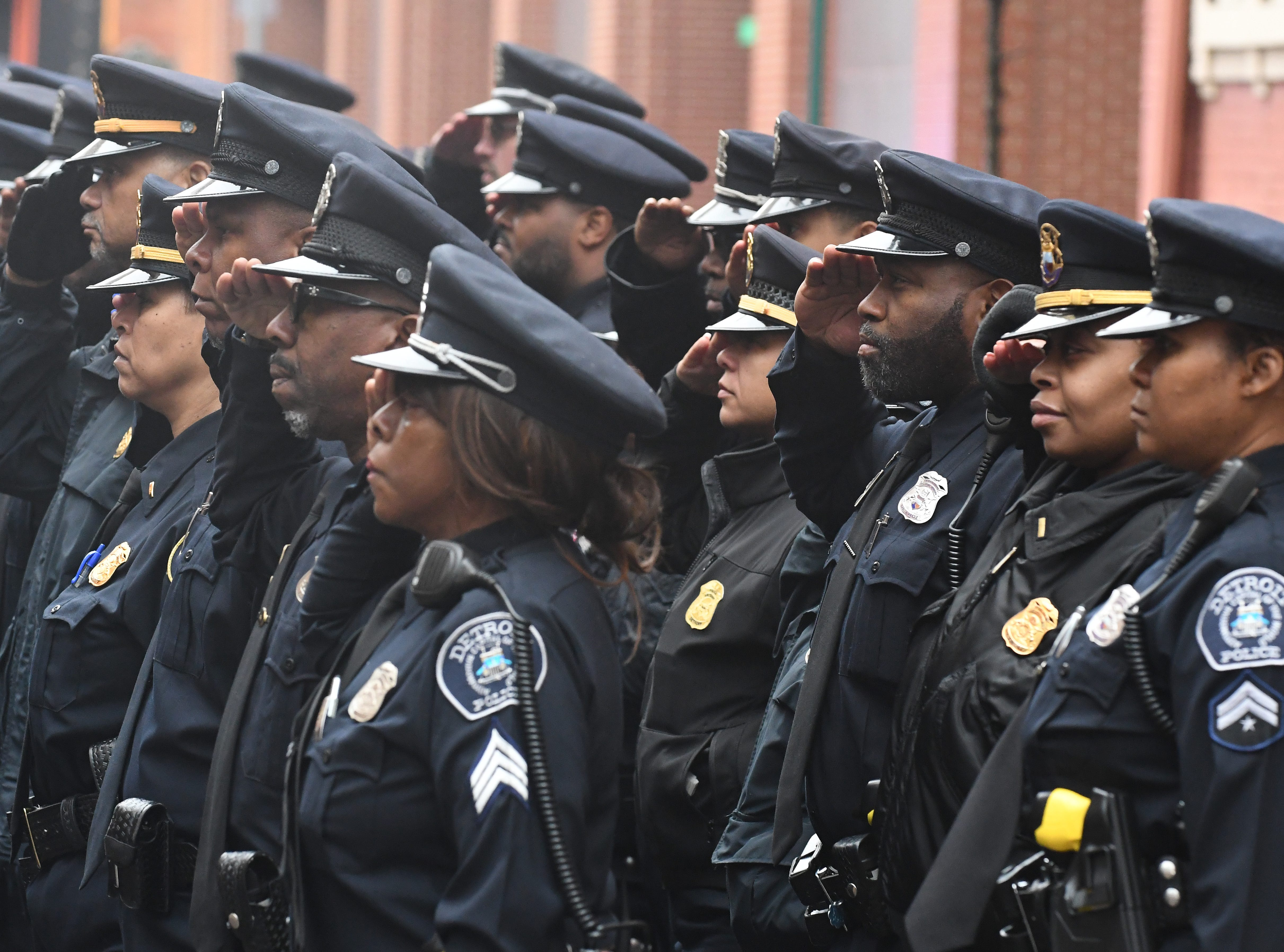 Detroit Police Officers stand at attention and salute outside the Old St. Mary's Church before the 46th Annual Detroit Police Interfaith Memorial Service. Detroit Police Department march and 46th Annual Detroit Police Interfaith Memorial Service to honor fallen officers at Old St. Mary's Church in Detroit, Michigan on May 3, 2019. (Image by Daniel Mears/ The Detroit News).