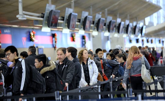 Travelers stand in line at the security entrance at Detroit Metro Airport.