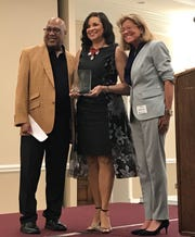 Vince McCraw, a former Detroit News online supervisor, presents Felecia Henderson, middle, with the Lifetime Achievement Award, which also was posthumously given to her husband, Angelo Henderson. Beth Konrad, SPJ Detroit president, is at right.