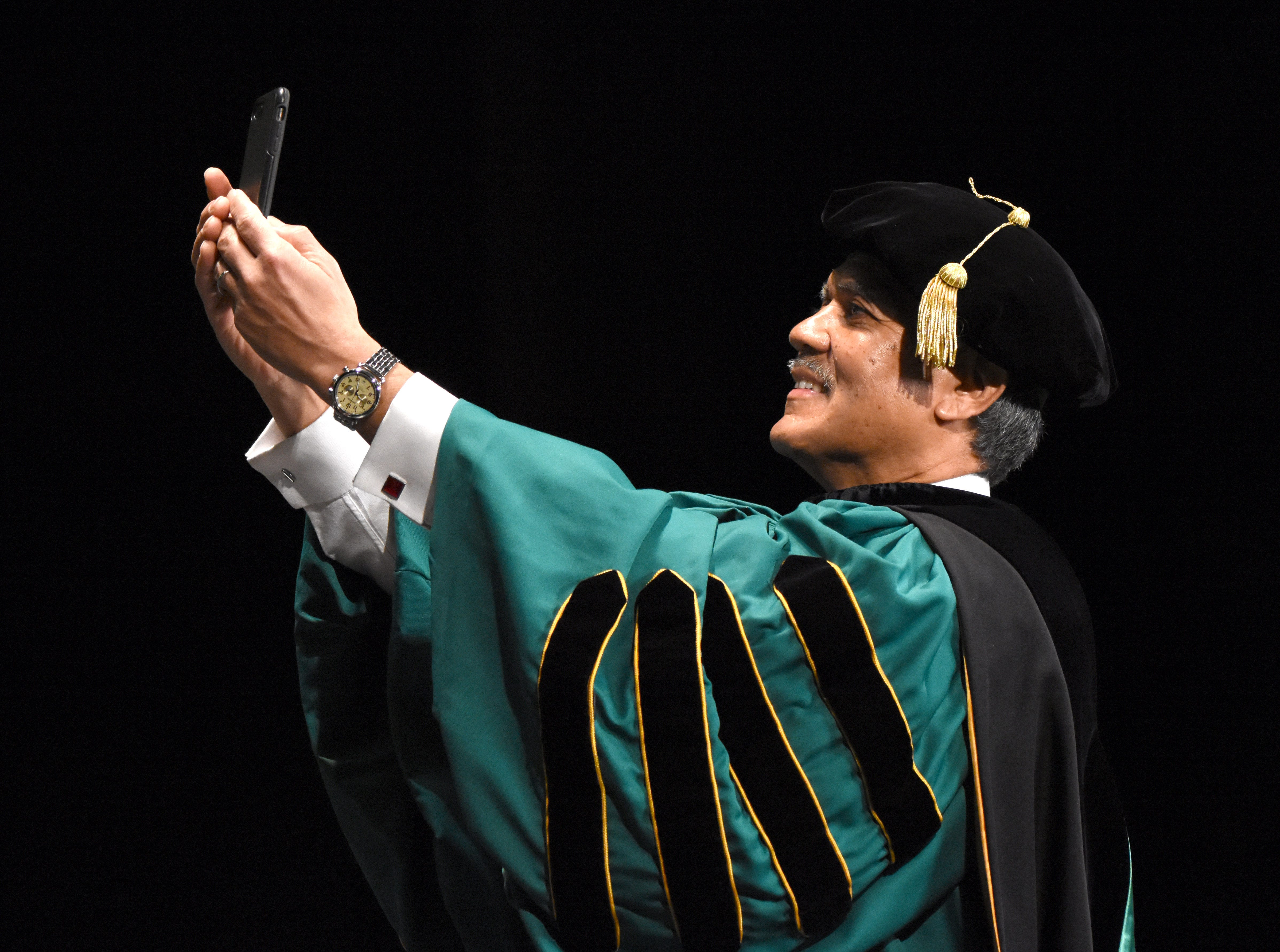 Wayne State University President M. Roy Wilson takes a selfie during commencement exercises at the Fox Theatre on Friday, May 3, 2019.