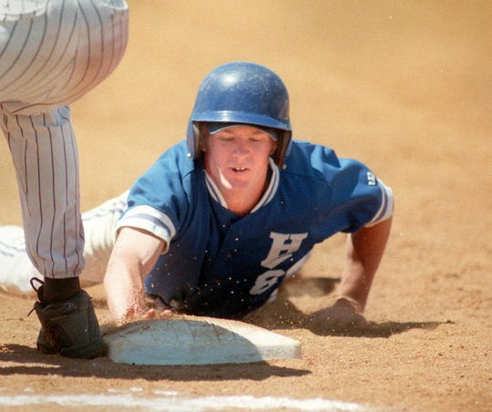 Horseheads' Jesse Hoobler slides back into first base during a state semifinal win over Greece Athena High School in Utica on June 12, 1999.