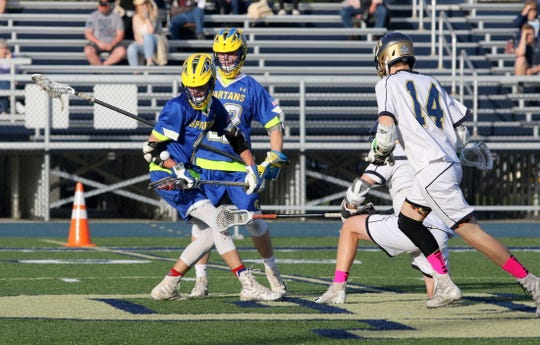 Gabe Thompson, left, of Maine-Endwell tries to control the ball off a faceoff against Elmira Notre Dame on May 2, 2019 at Notre Dame. Also pictured are Notre Dame's Stephen Schmidt (14) and Owen Spring, and M-E's Kevin Vicari.