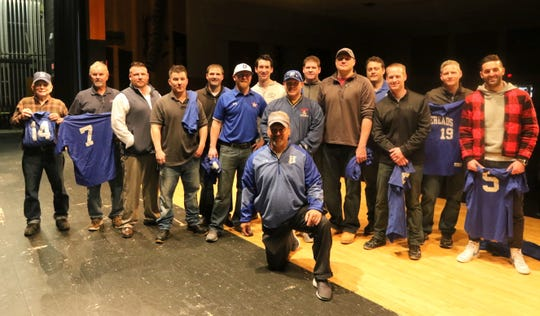 Head coach Jeff Limoncelli, front, poses with the 1999 state championship Horseheads baseball team and the father of one of the players who could not attend May 3, 2019 at Horseheads High School.