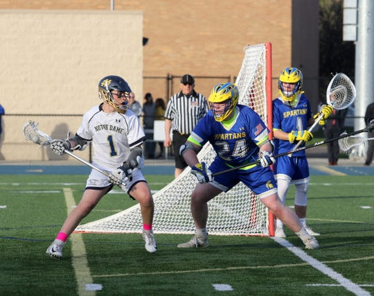 Owen Spring of Elmira Notre Dame looks for an opening as Maine-Endwell's Brennan McQuade defends in front of goalie Samuel Toton in boys lacrosse May 2, 2019 at Notre Dame High School.