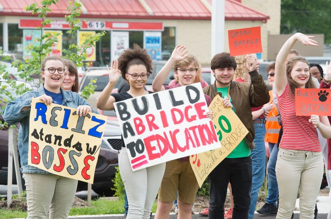 Reitz High School student activist holds signs and wave at cars before marching across the crosswalk at U.S. 41 and Washington Ave. to send a message to the City of Evansville to solicit funds from the General Fund and prioritize their request of a pedestrian bridge to legislators.