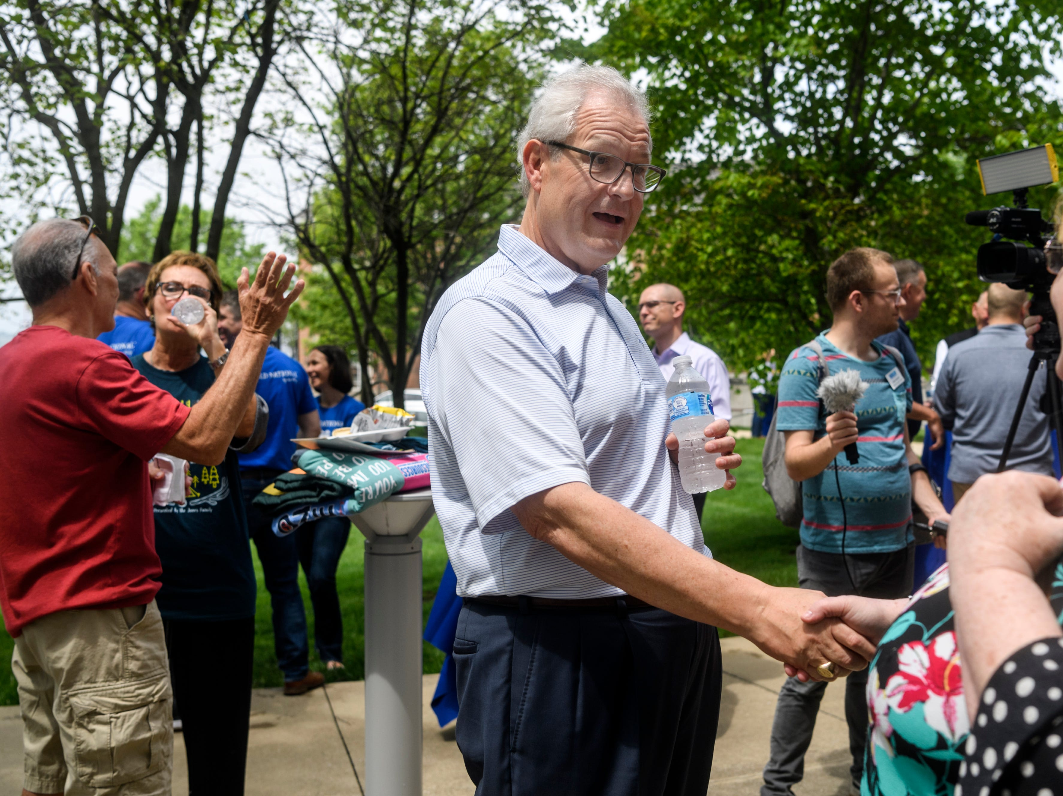 Bob Jones, center, the retiring Old National Bank chief executive officer, receives a long line of congratulations from people attending his farewell party outside of Old National Bank's headquarters in downtown Evansville, Ind., Friday, May 3, 2019.