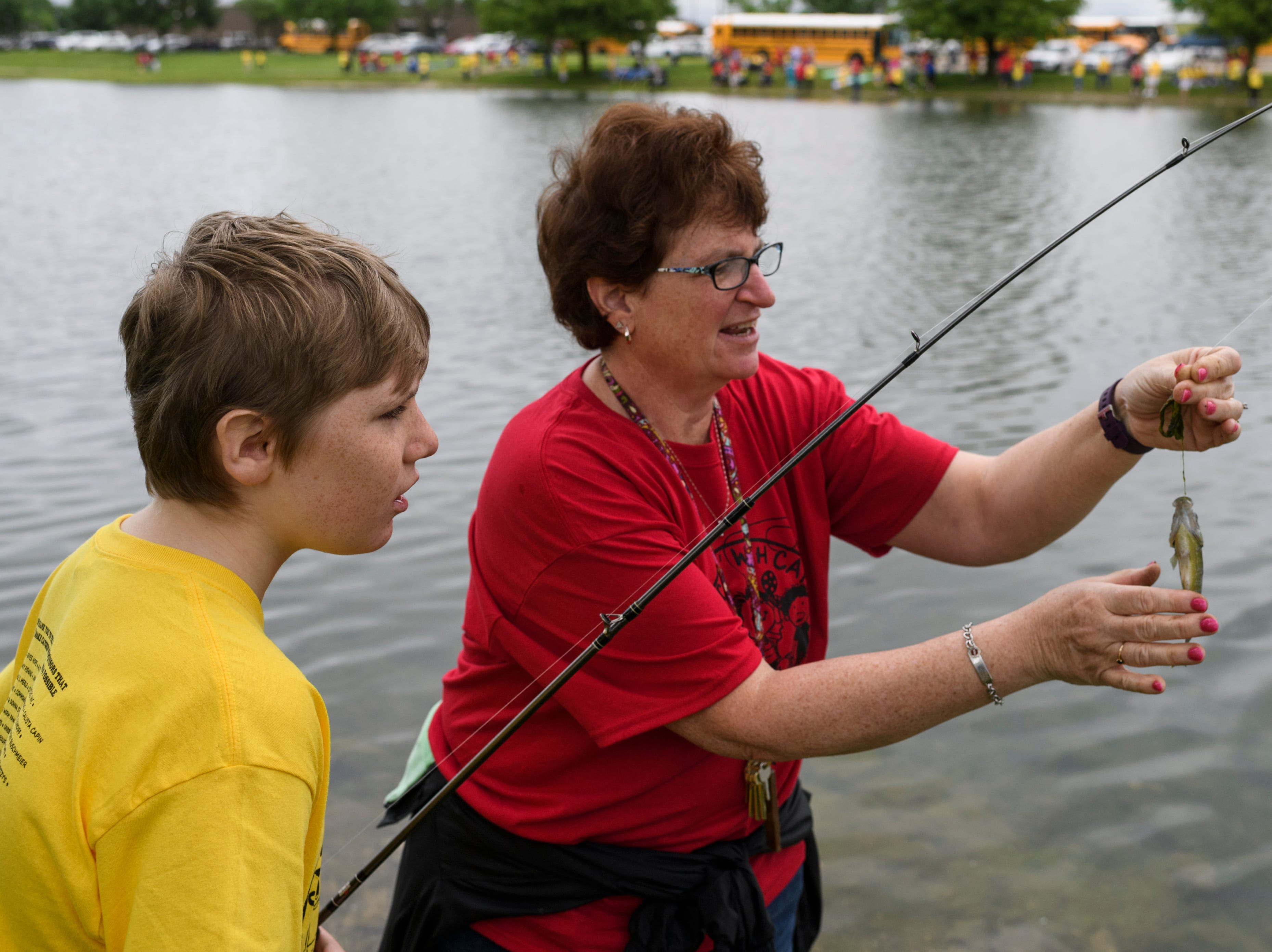 """Oscar Farley, left, a North Junior High student, receives help from special education aide Maryann Dunbar, right, as they get his first caught fish off the line during the 12th annual """"Catchin' with Capin"""" event at Eagle Lake in Evansville, Ind., Friday, May 3, 2019. The annual outing gives children with disabilities an opportunity to enjoy a day of fishing."""