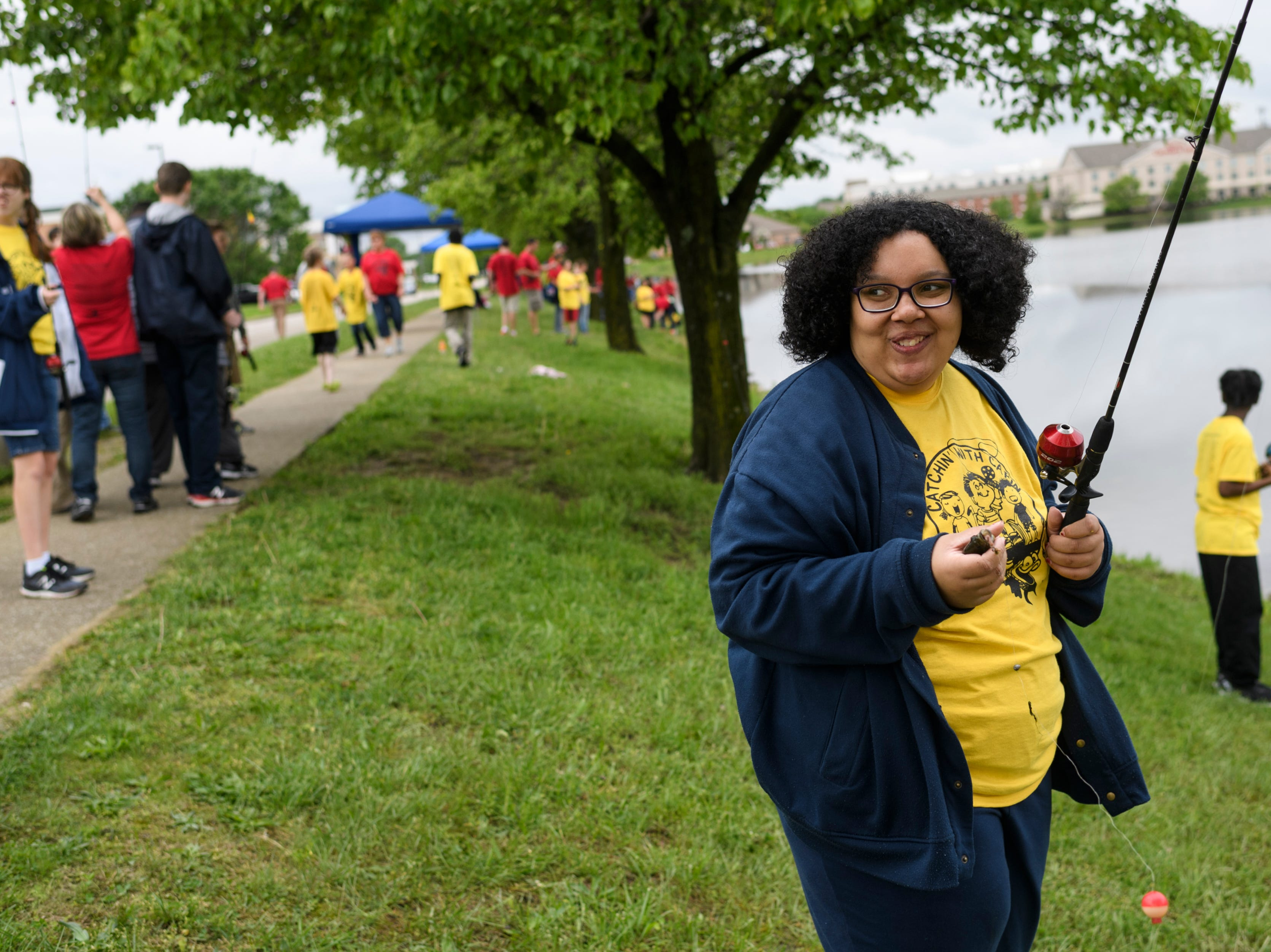 """Summer Combs, a Bosse High School student, smiles while holding a Bluegill fish she caught during the 12th annual """"Catchin' with Capin"""" event at Eagle Lake in Evansville, Ind., Friday, May 3, 2019."""