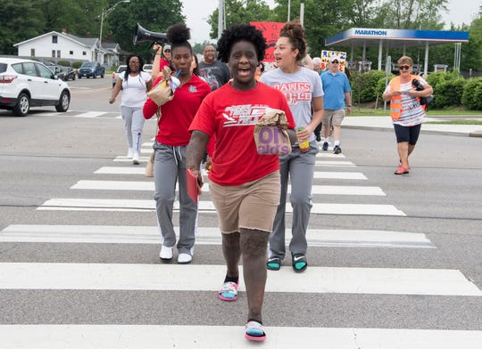 Bosse High School students Vanessa Johnson, front, BreAsia Williams, left, and Miakhara Hazelwood, right, lead a group of activist across the crosswalk at U.S. 41 and Washington Ave. to send a message to the City of Evansville to solicit funds from the General Fund and prioritize their request of a pedestrian bridge to legislators.