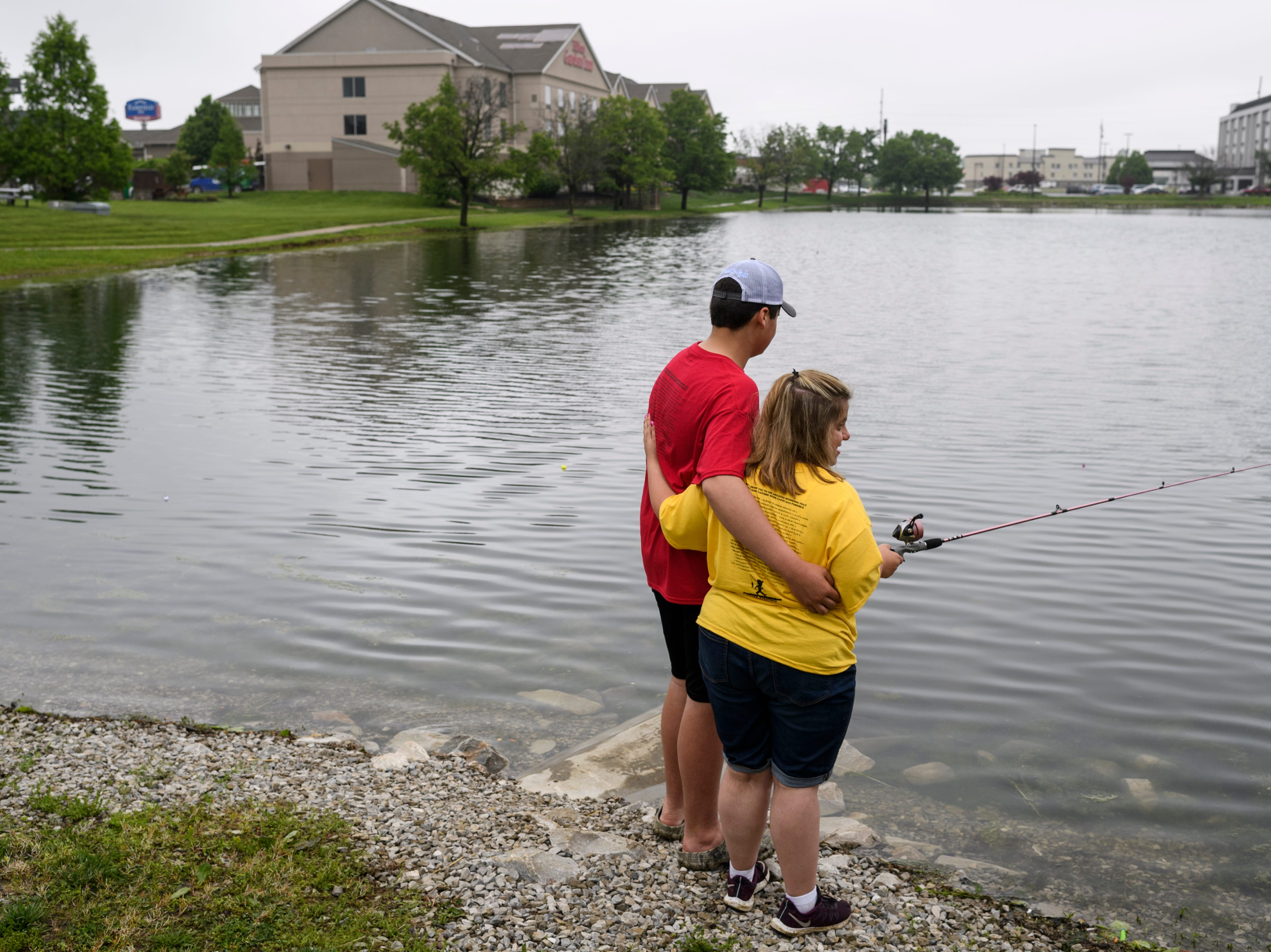 """Connor King, a student volunteer from Mt. Vernon High School, embraces Kylee Ricketts, right, his girlfriend Kelcey Rickett's sister, as they fish together during the 12th annual """"Catchin' with Capin"""" event at Eagle Lake in Evansville, Ind., Friday, May 3, 2019. King is a sponsored competitive fisherman who often competes in catfishing tournaments."""