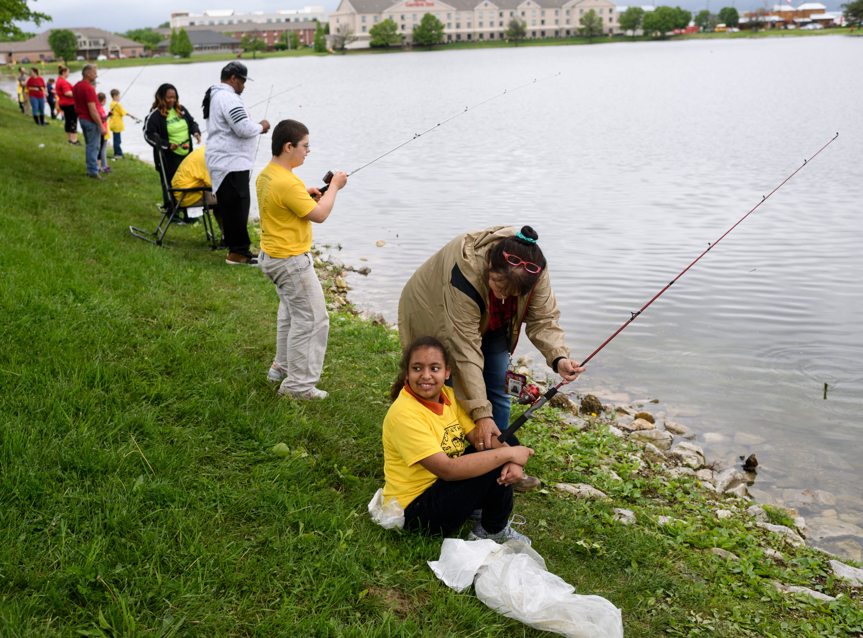 """Charlotte Skelton, a special education aide, helps North Junior High student Angel Keeper cast her line as they fish with others during the 12th annual """"Catchin' with Capin"""" event at Eagle Lake in Evansville, Ind., Friday, May 3, 2019."""