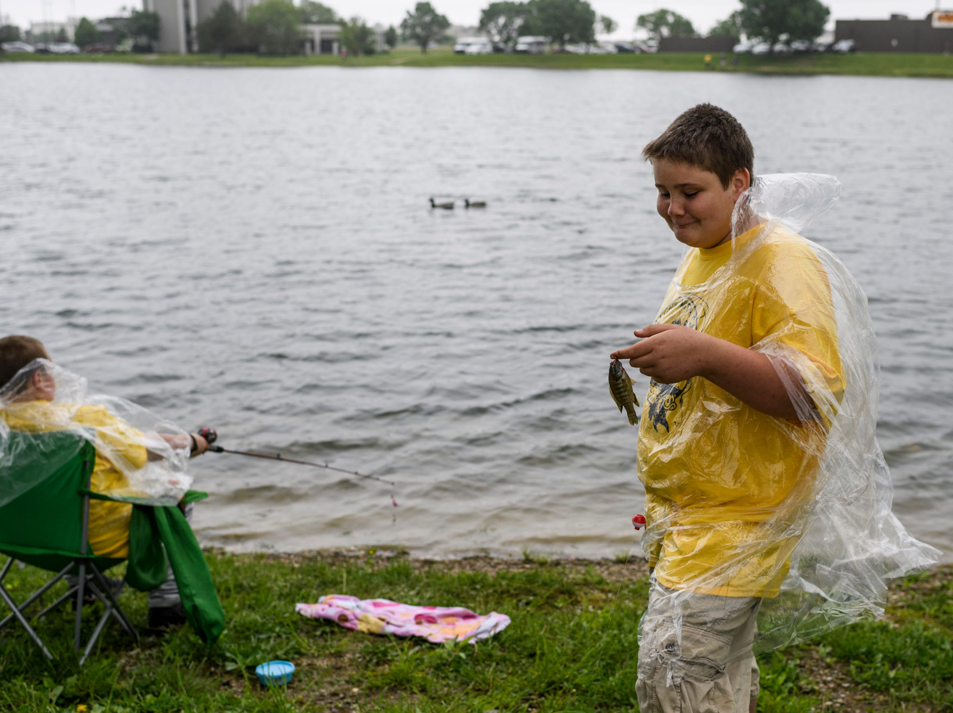 """Mt. Vernon Junior High student Anthony Muller, right, glances down proudly at his most recent catch as Gabe Hatch, left, waits for a bite on his line during the 12th annual """"Catchin' with Capin"""" event at Eagle Lake in Evansville, Ind., Friday, May 3, 2019."""