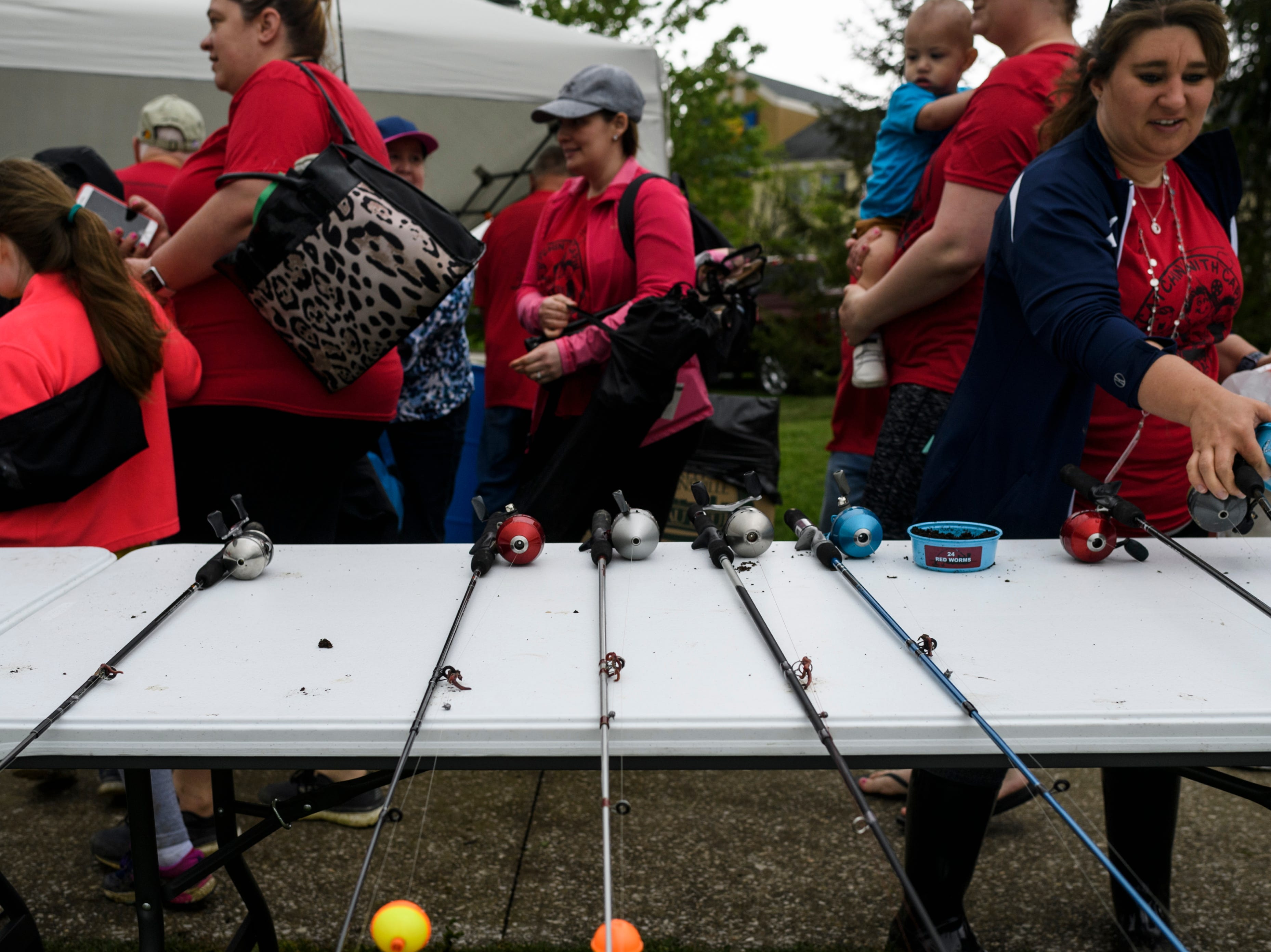"""Fishing poles and worms are provided for students attending the 12th annual """"Catchin' with Capin"""" event at Eagle Lake in Evansville, Ind., Friday, May 3, 2019."""