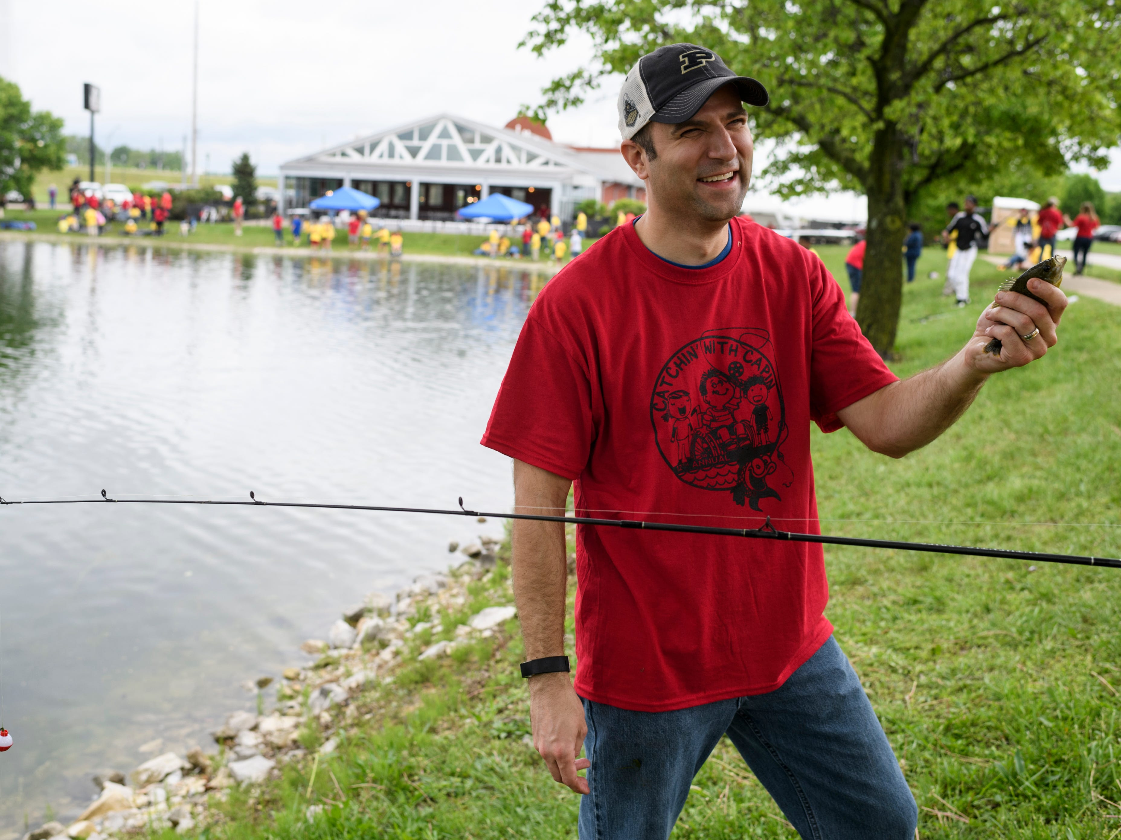 """Ryan Mayer, a volunteer, smiles after showing Alexis Niemeier how to kiss a fish during the 12th annual """"Catchin' with Capin"""" event at Eagle Lake in Evansville, Ind., Friday, May 3, 2019. Mayer works with Kyle Capin, the event's founder, at Evansville Water and Sewer Department."""