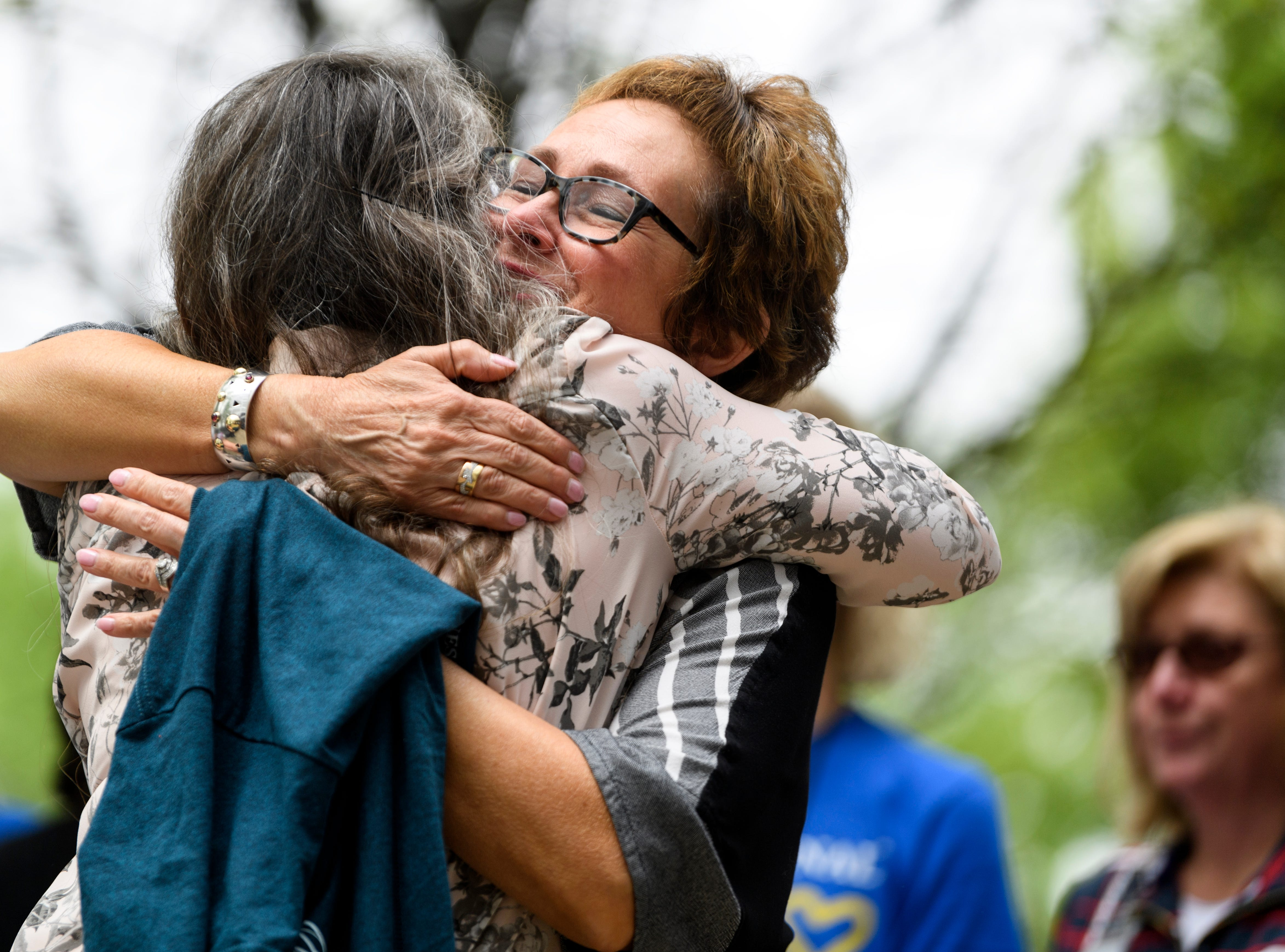 Youth Resources Executive Director Laura Ferguson, front, embraces Lisa Jones, back, wife of retiring Old National Chief Executive Officer Bob Jones, during a farewell party for Jones at Old National Bank in downtown Evansville, Ind., Friday, May 3, 2019.