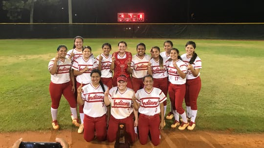 The Immokalee softball team poses in front of the scoreboard after beating Lely, 4-0, for the Indians' first-ever district title Thursday. The Indians host Mariner on Wednesday in the regional quarterfinals.