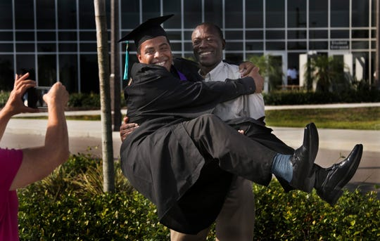 Reggie Haines Jr. jumps into the arms of his father Reggie Haines as his mother, Sandy Schoenberg, takes a photo before his graduation from Florida Southwestern State College on Friday, May 3, 2019, in Fort Myers.