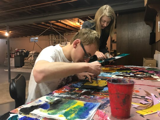 Austin Olsen works with Kasey Hock on a painting in the studio in his parents' basement.