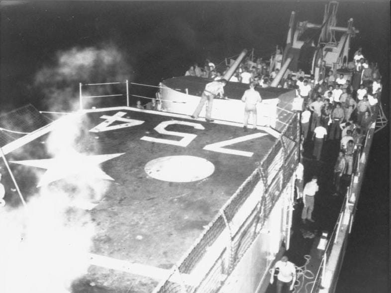 The remaining crew of the USS Frank E. Evans musters on deck after the ship was cut in half it a collision with the HMAS Melbourne, an Australian aircraft carrier, during a training exercise in 1969.