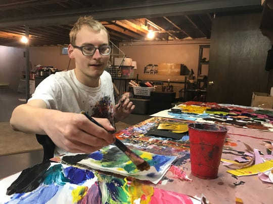 Austin Olsen works on a painting in the studio in his parents' basement.