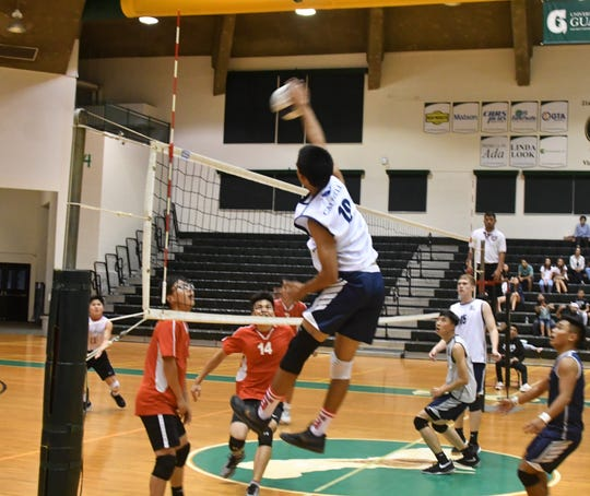 Harvest outside hitter Mason Caldwell slams the ball down on a no-block situation from the St. John's Knights in IIAAG Boys Volleyball playoff action May 2 at the UOG Calvo Field House.