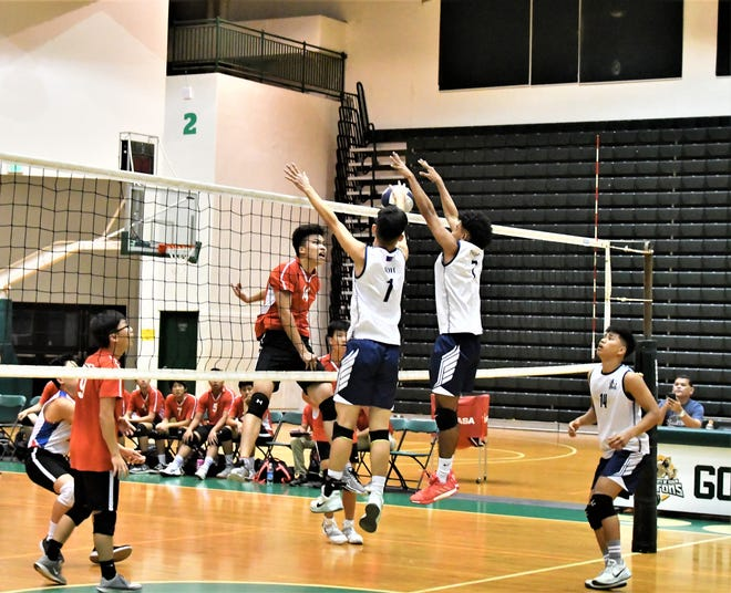 No. 14 Kyle Liu, left, tools the Harvest block of JR Noh and Alan Thomas  in IIAAG Boys Volleyball action May 2 at the UOG Calvo Field House.