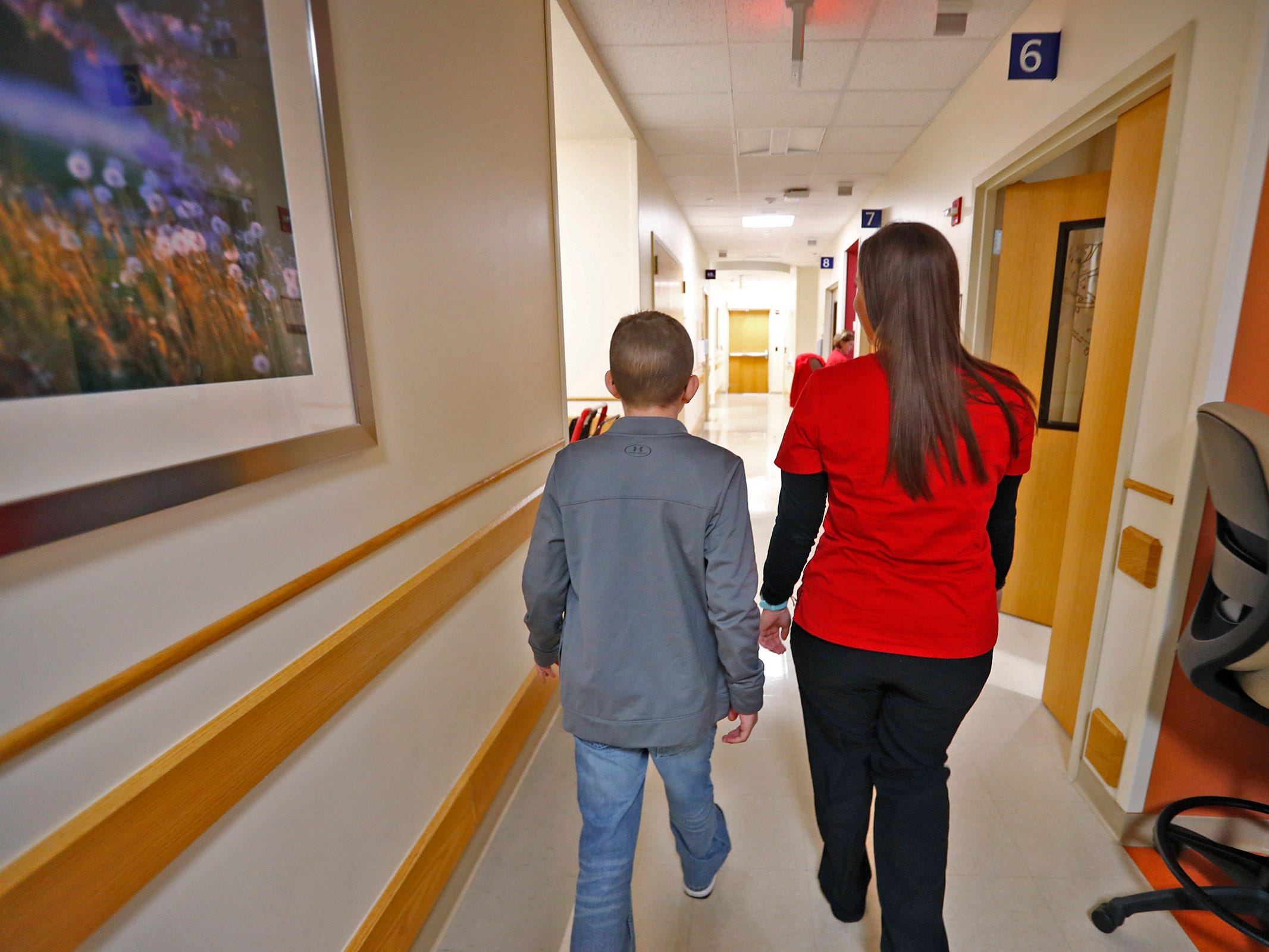 Cameron Kirk, left, walks with his nurse, Rhea Watson at the Center for Pediatric Cancer and Blood Disorders at the Riley Outpatient Center, Friday, April 19, 2019.  Watson was treated for leukemia when she was younger, diagnosed ten years ago, and now is an RN taking care of similar patients, like Cameron who has diagnosed with the same cancer one year ago.  Now Watson is hoping to be the Leukemia & Lymphoma Society Woman of the Year, in a fundraising effort which ends May 18, 2019.