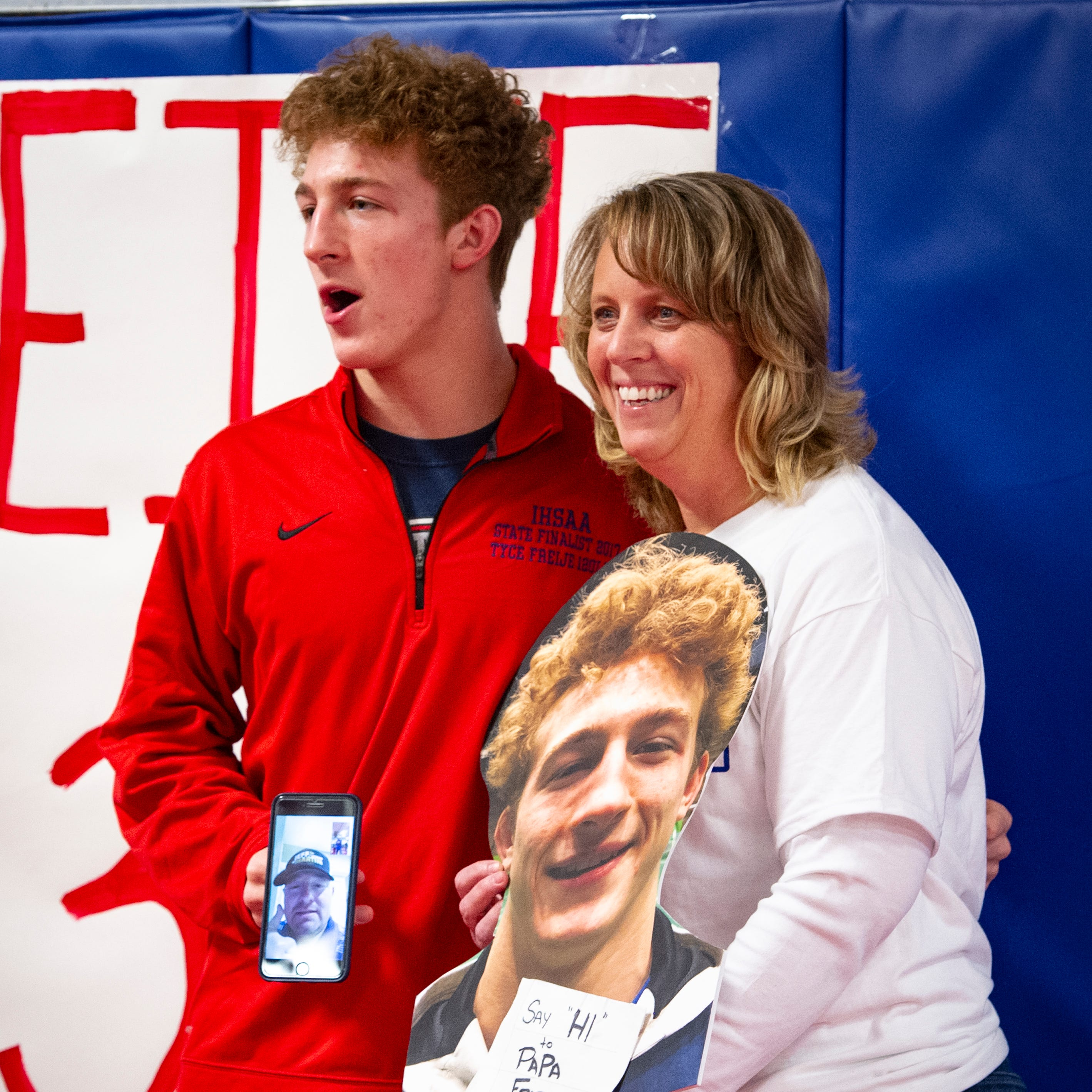 Roncalli wrestler Tyce Freije poses for photos with his mom, Jodie Freije, and his father, T.J. Freije, pictured on the phone, Feb, 19, 2019.