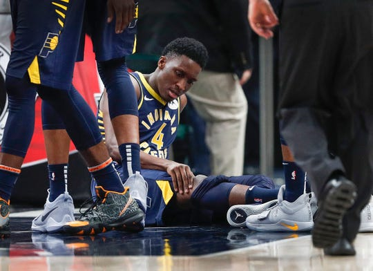 Pacers guard Victor Oladipo holds his right knee after going down with an injury in the second quarter of their game against the Toronto Raptors at Bankers Life Fieldhouse, Jan. 23, 2019.