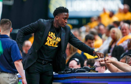 Pacers guard Victor Oladipo greets the scorers' table worker in the first half of their game at Bankers Life Fieldhouse on April 21, 2019.