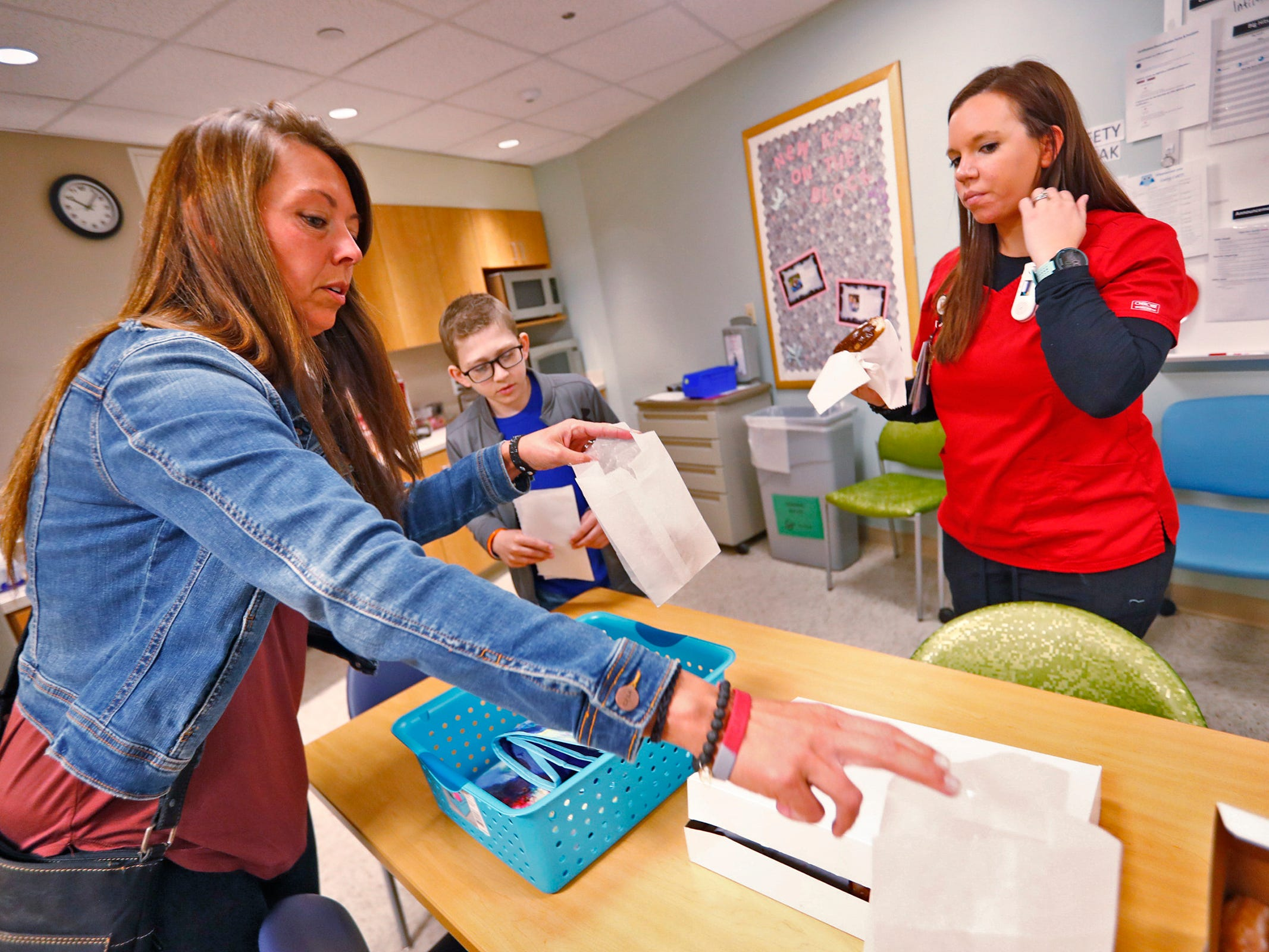 Cameron Kirk, center, gets ready to have doughnuts with his mother, Carrie Kirk, left, and his nurse, Rhea Watson, right, at the Center for Pediatric Cancer and Blood Disorders at the Riley Outpatient Center, Friday, April 19, 2019.  Watson was treated for leukemia when she was younger, diagnosed ten years ago, and now is an RN taking care of similar patients, like Cameron who has diagnosed with the same cancer one year ago.  Now Watson is hoping to be the Leukemia & Lymphoma Society Woman of the Year, in a fundraising effort which ends May 18, 2019.