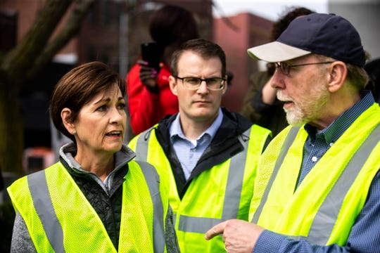 Iowa Gov. Kim Reynolds, talks with U.S. Rep. Dave Loebsack, D-Iowa, (right) while they tour areas impacted by floodwater, with Lt. Gov. Adam Gregg (center) and officials, Friday, May 3, 2019, in downtown Davenport, Iowa.