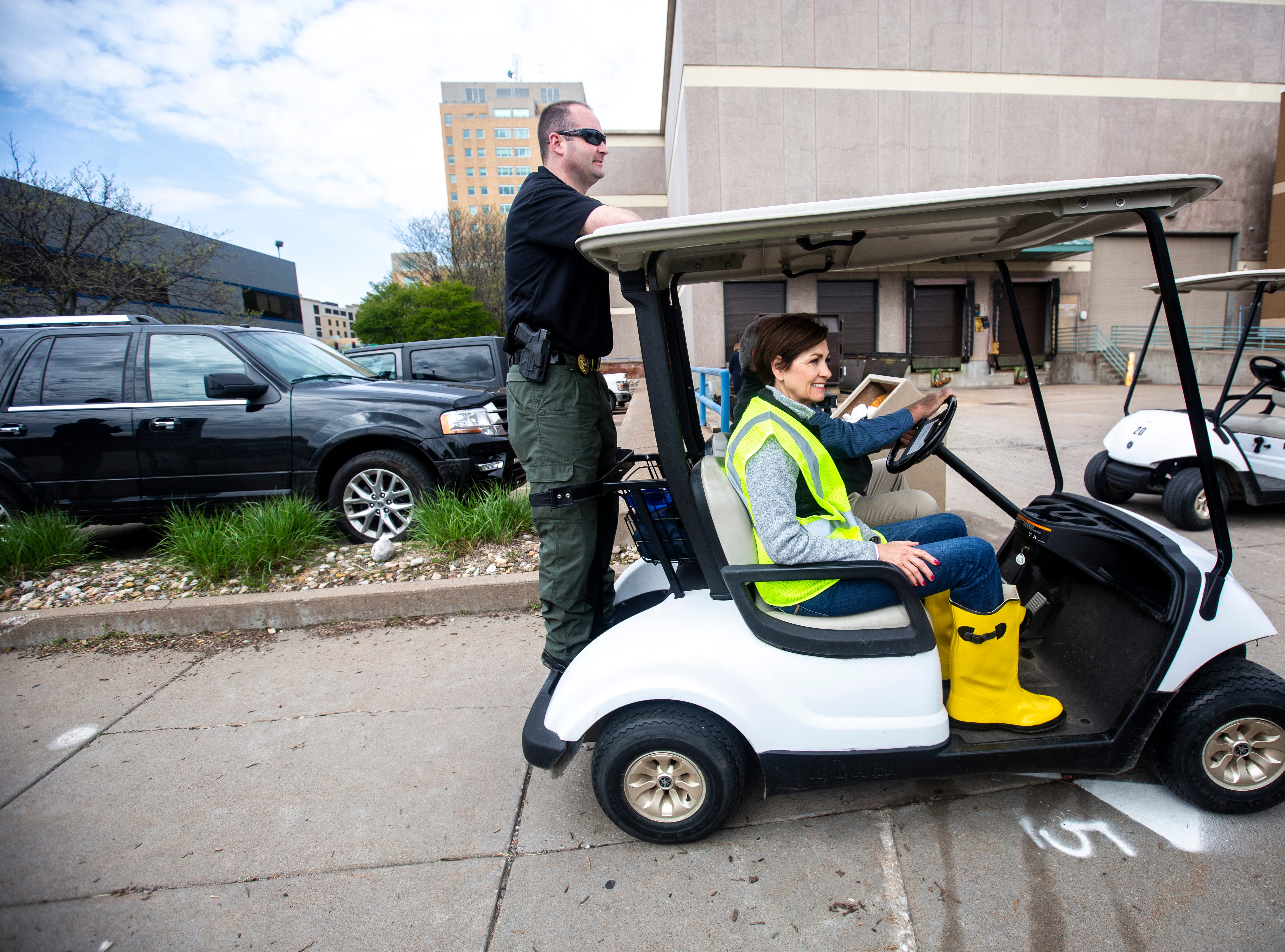 Iowa Gov. Kim Reynolds, gets a ride in a golf cart, while touring areas impacted by floodwater, Friday, May 3, 2019, in downtown Davenport, Iowa.
