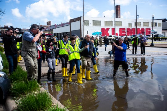 Iowa Gov. Kim Reynolds, walks into floodwater while on a tour of areas impacted, with Lt. Gov. Adam Gregg, U.S. Rep. Dave Loebsack, D-Iowa, and Davenport Mayor Frank Klipsch Friday, May 3, 2019, along Pershing Avenue in downtown Davenport, Iowa.