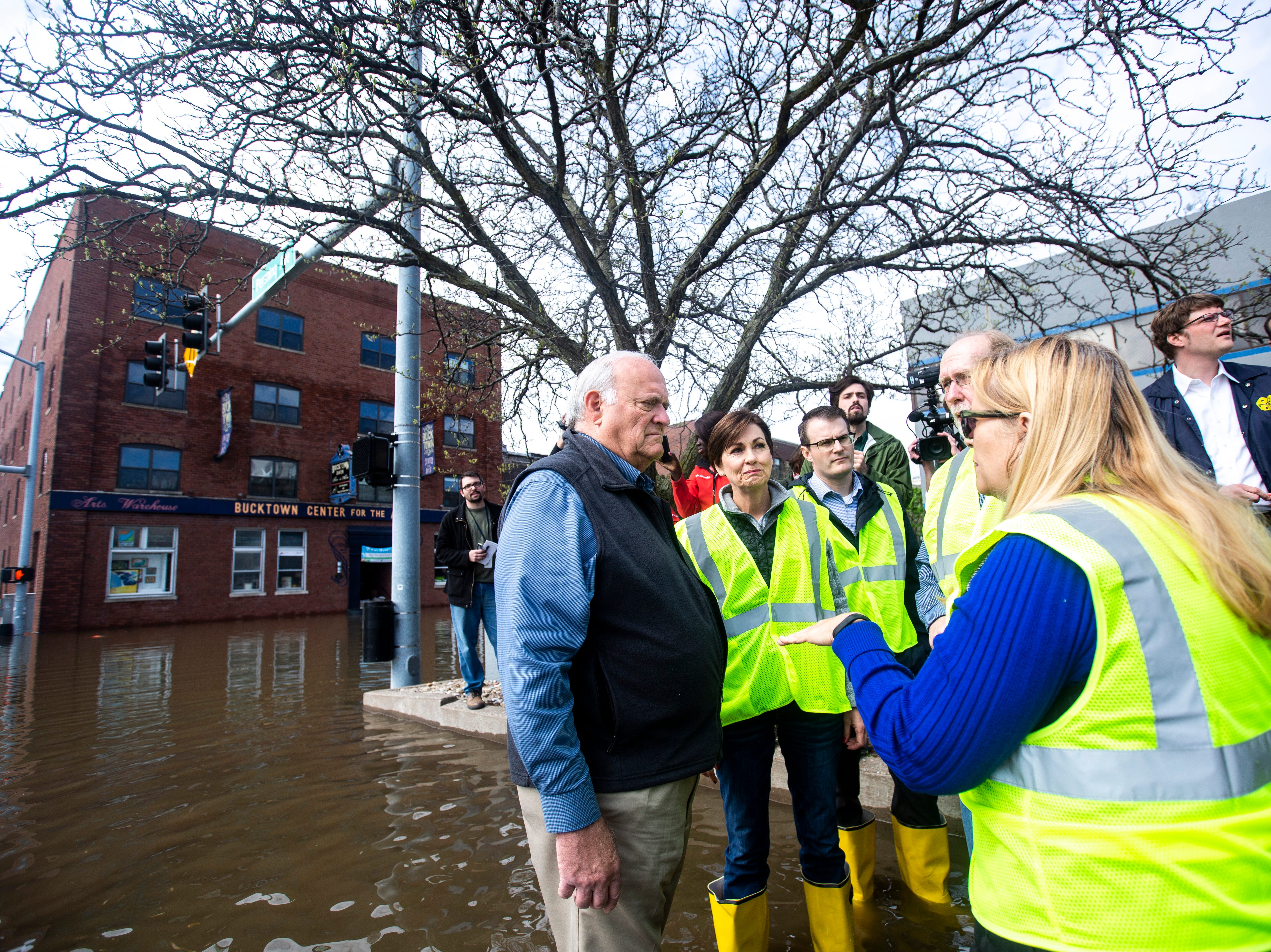 Davenport Mayor Frank Klipsch (from left) stands in floodwater while on a tour of areas impacted, with Iowa Gov. Kim Reynolds, Lt. Gov. Adam Gregg and U.S. Rep. Dave Loebsack, D-Iowa, Friday, May 3, 2019, along Pershing Avenue in downtown Davenport, Iowa.