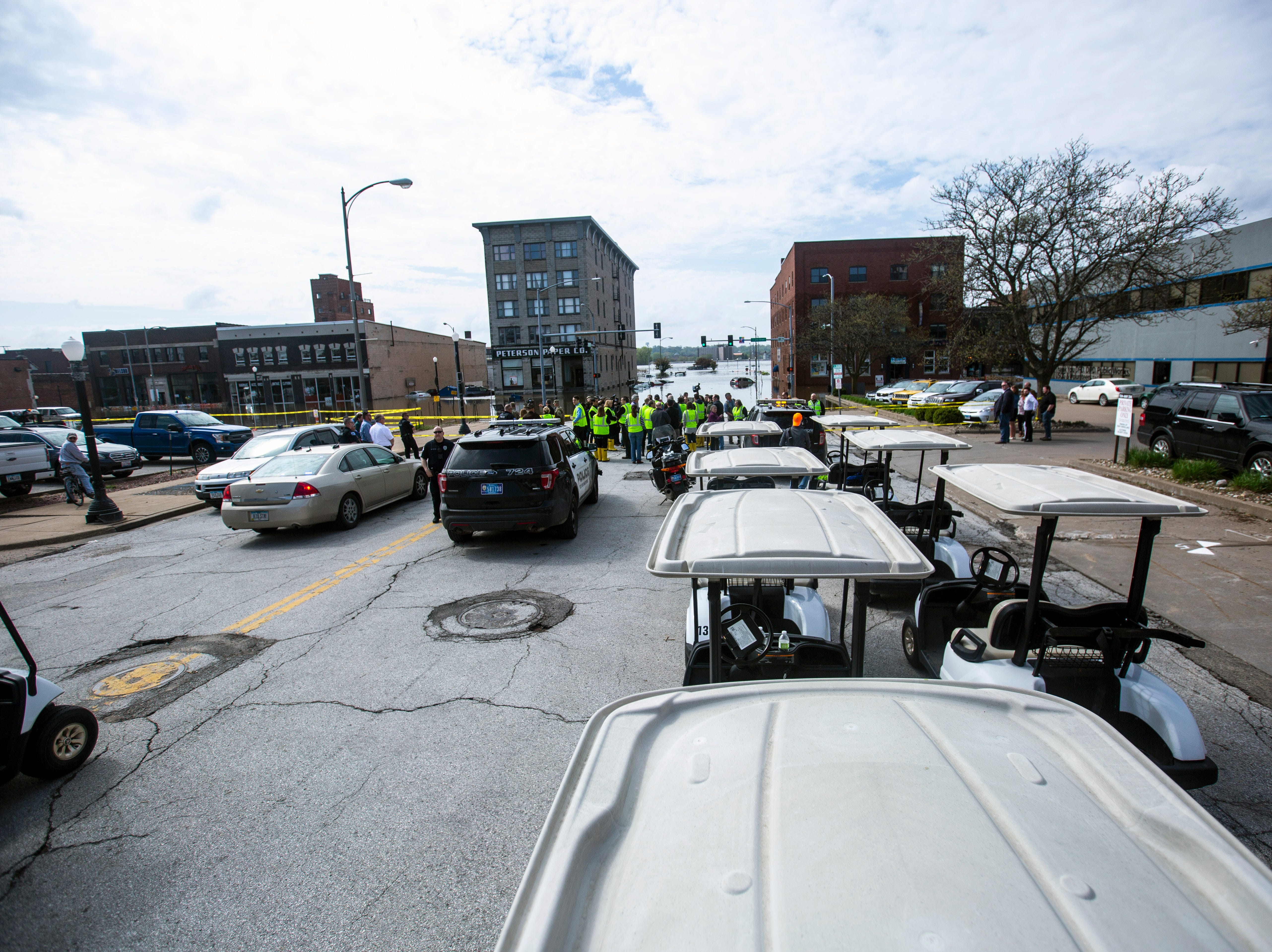 A group of golf carts park along Pershing Avenue while Iowa Gov. Kim Reynolds, tours areas impacted by floodwater, Friday, May 3, 2019, in downtown Davenport, Iowa. The temporary flood barrier at Pershing Avenue and River Drive failed Tuesday afternoon.