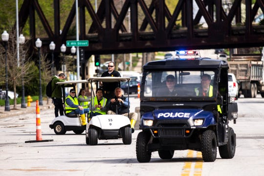 Iowa Gov. Kim Reynolds, rides in the second golf cart driven by Davenport Mayor Frank Klipsch with a police escort during tours areas impacted by floodwater, Friday, May 3, 2019, in downtown Davenport, Iowa. U.S. Rep. Dave Loebsack, D-Iowa, second from left behind in third golf cart.