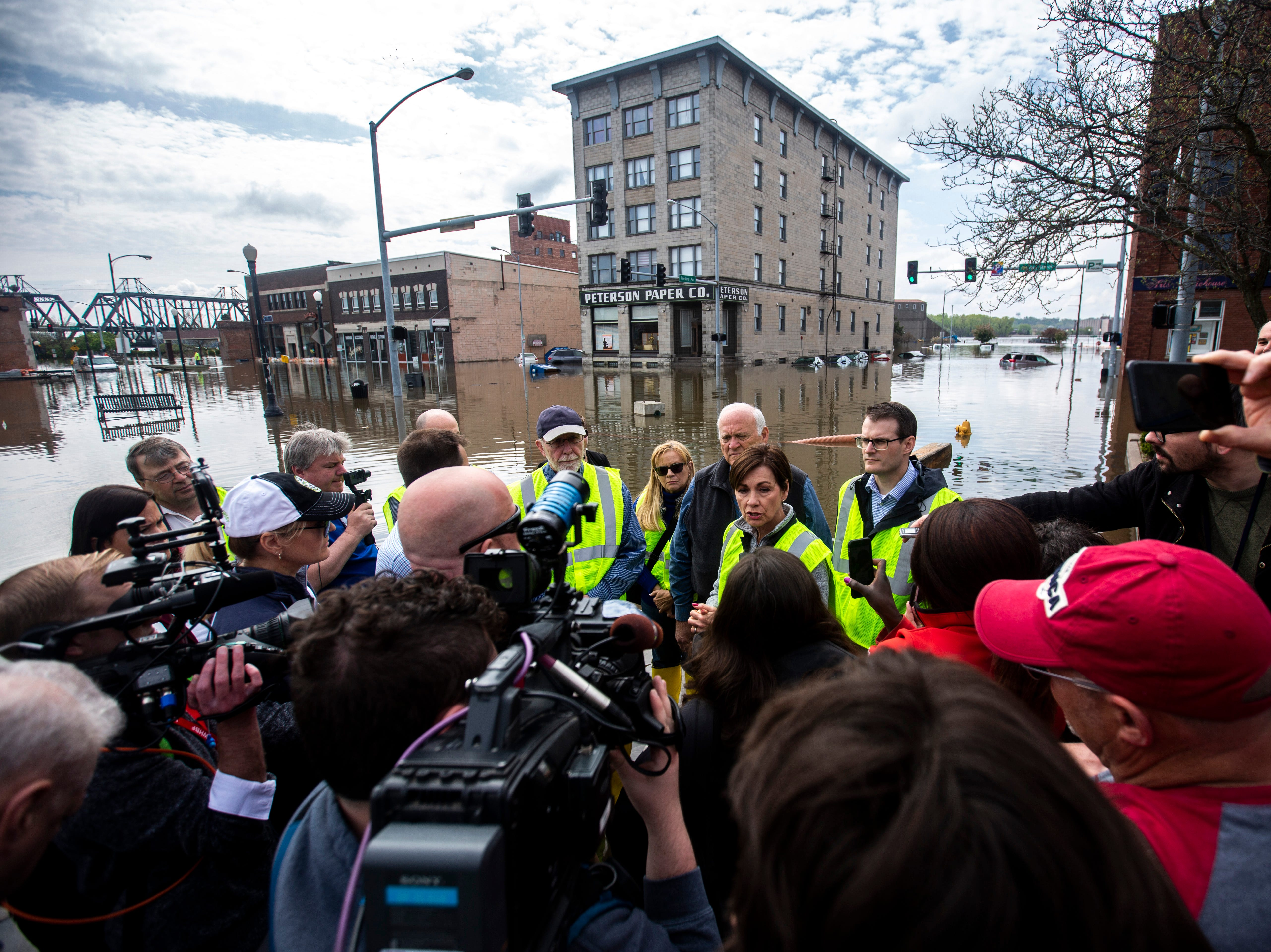 Iowa Gov. Kim Reynolds, talks with reporters briefly while touring areas impacted by floodwater, with U.S. Rep. Dave Loebsack, D-Iowa, Lt. Gov. Adam Gregg, Friday, May 3, 2019, in downtown Davenport, Iowa.