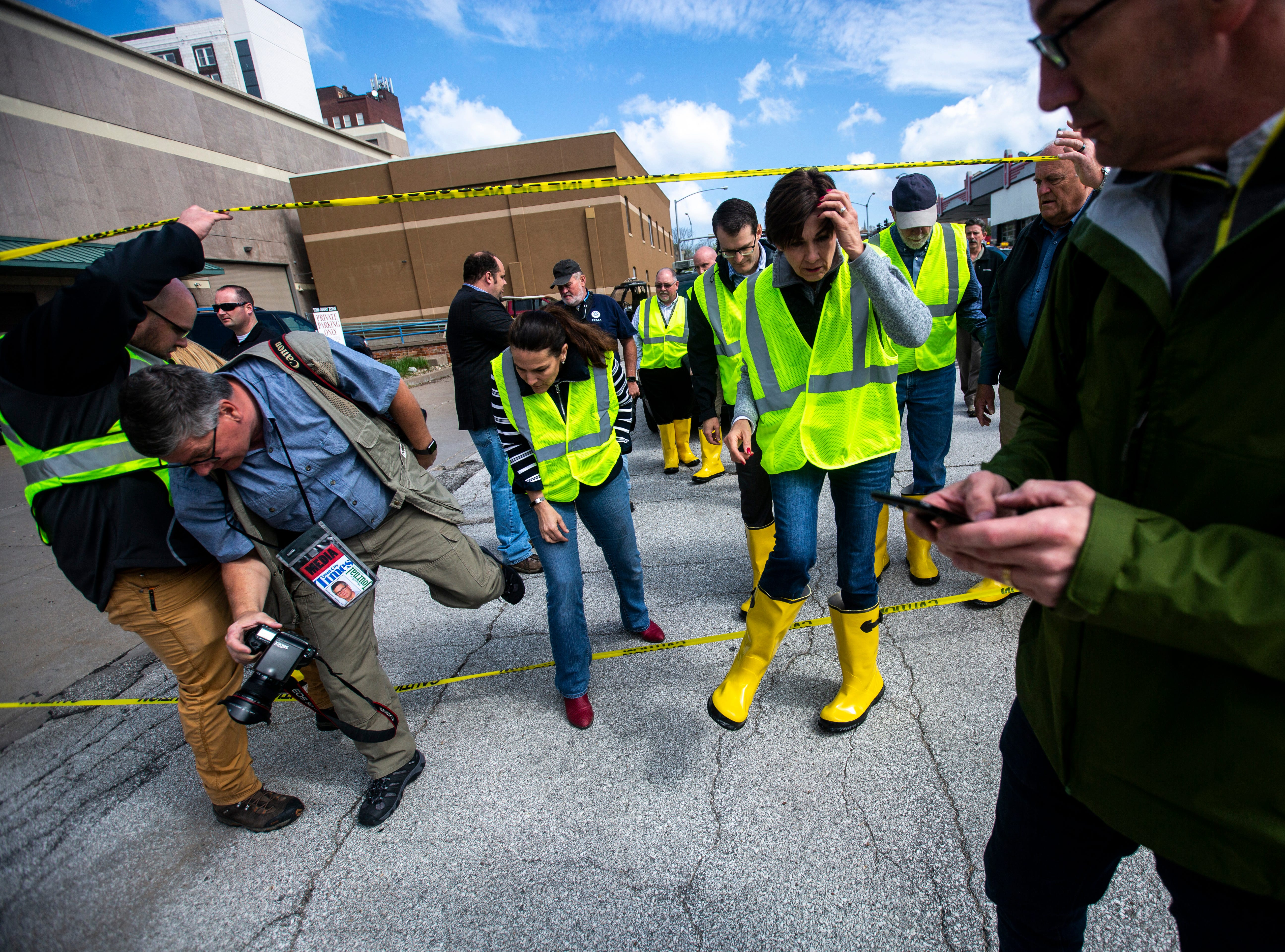 Iowa Gov. Kim Reynolds, steps under a yellow police tape line along Pershing Avenue while touring areas impacted by floodwater, with Lt. Gov. Adam Gregg and U.S. Rep. Dave Loebsack, D-Iowa, Friday, May 3, 2019, in downtown Davenport, Iowa.