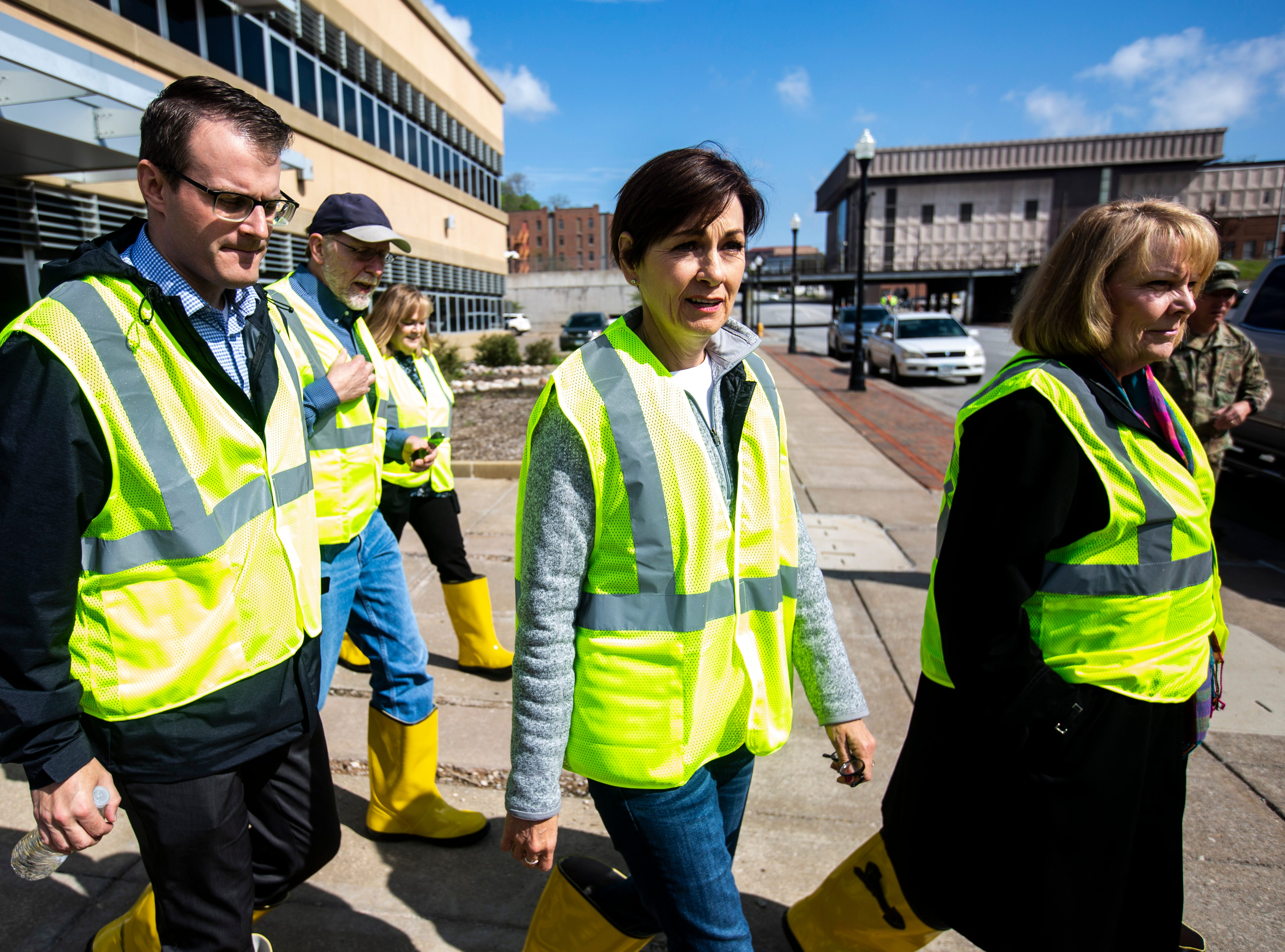Iowa Gov. Kim Reynolds, second from right, walks out of the police station before taking a tour of areas impacted by floodwater, with Lt. Gov. Adam Gregg, far left, and U.S. Rep. Dave Loebsack, D-Iowa, Friday, May 3, 2019, in downtown Davenport, Iowa.