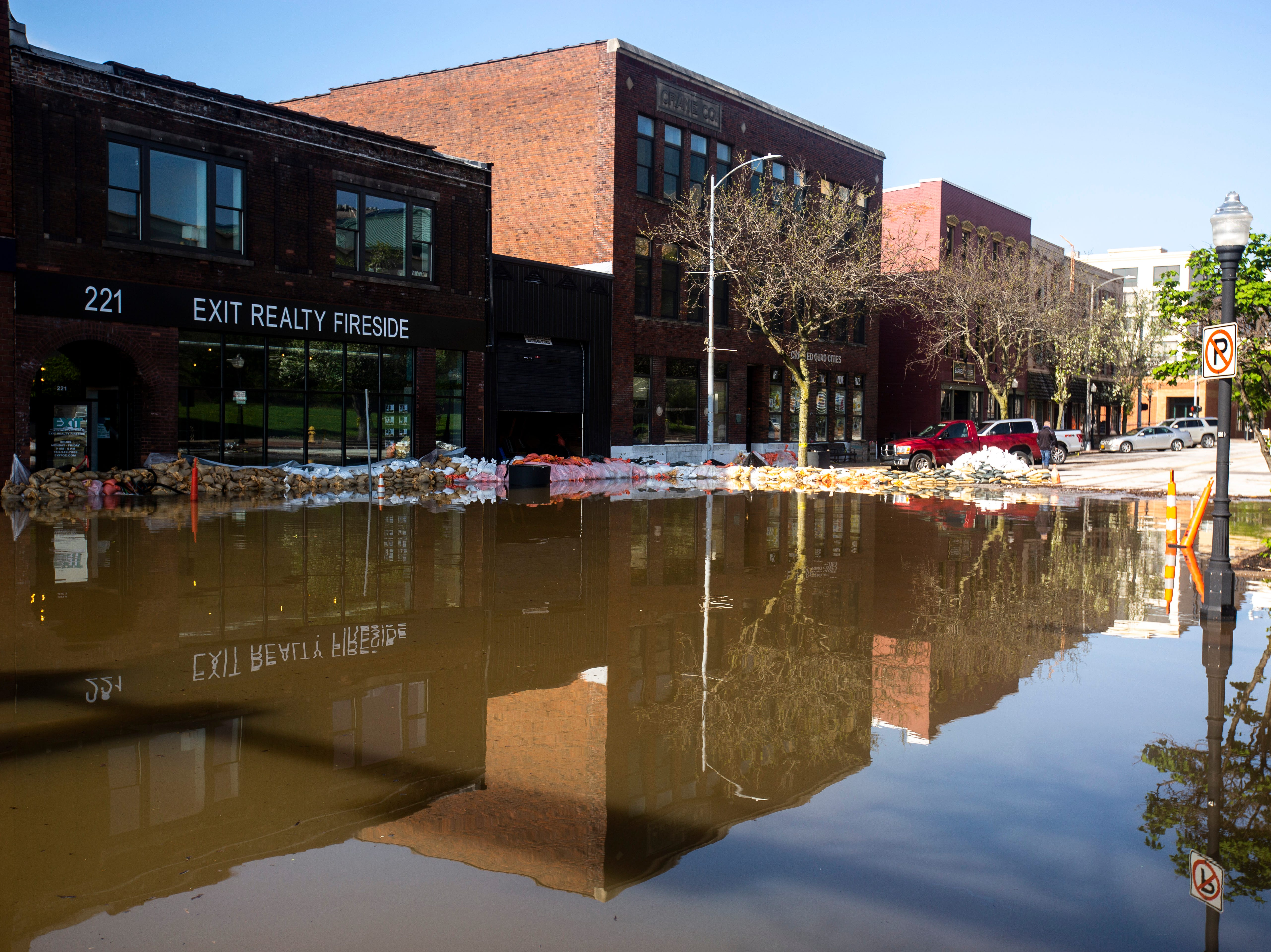 Businesses are reflected along 2nd Street in floodwaters, Friday, May 3, 2019, in downtown Davenport, Iowa.