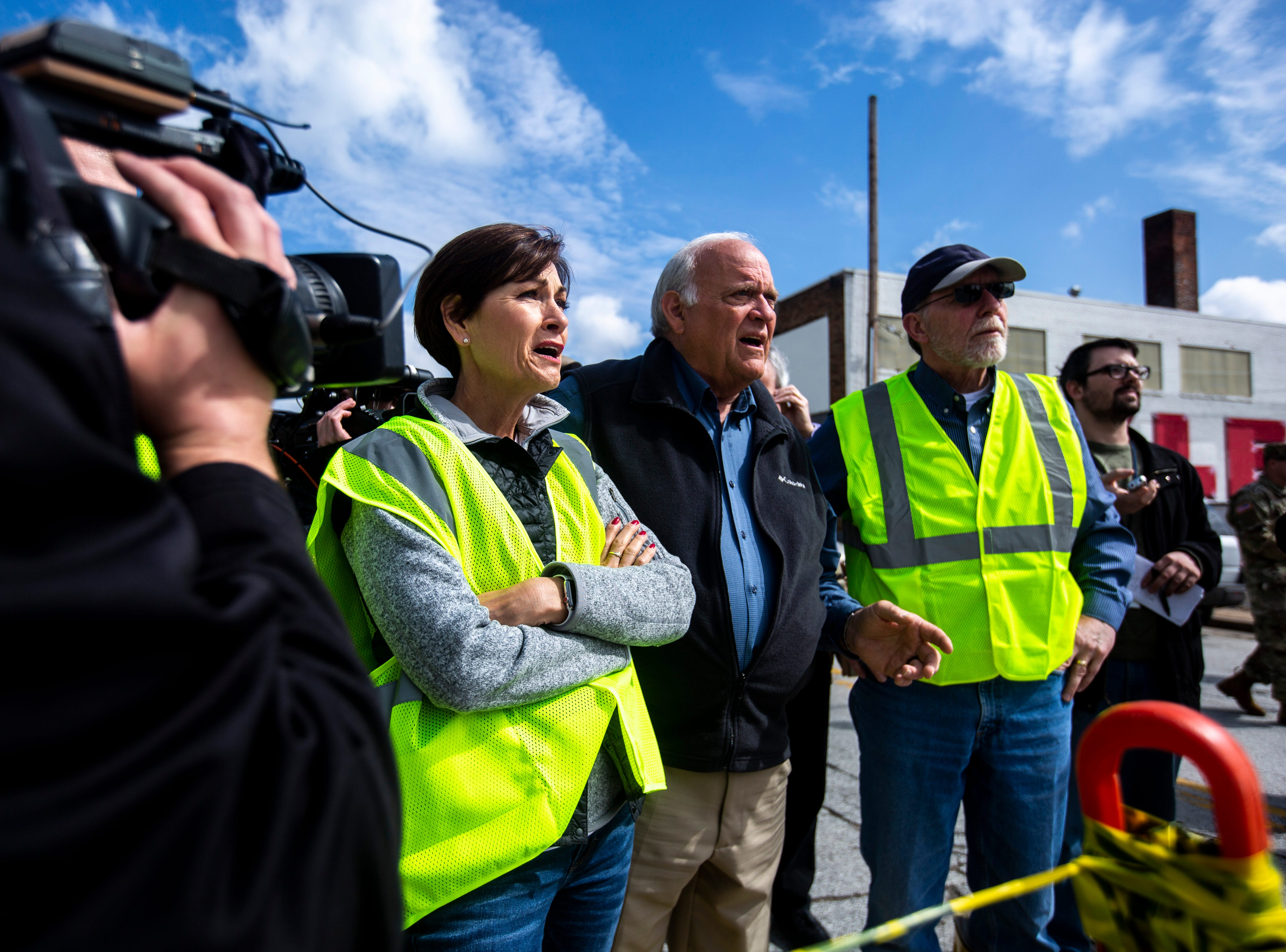 Iowa Gov. Kim Reynolds, looks out past a police line towards Pershing Avenue while touring areas impacted by floodwater, with Davenport Mayor Frank Klipsch and U.S. Rep. Dave Loebsack, D-Iowa, Friday, May 3, 2019, in downtown Davenport, Iowa. The temporary flood barrier at Pershing Avenue and River Drive failed Tuesday afternoon.