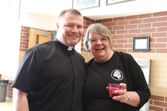 Father Adam Kane and parishioner Ernie Meiners pause to share a smile at the annual Adult Social sponsored by All Saints Catholic Church and held at Knoxville Catholic High School Friday, April 26.