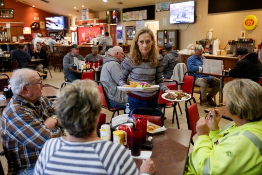 Dawn Summers brings out a table's food during lunch service, Friday, May 3, 2019 at Tick Tock Tavern in Lafayette.