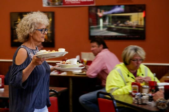 Tina Taylor carries out a table's order during lunch service, Friday, May 3, 2019 at Tick Tock Tavern in Lafayette.