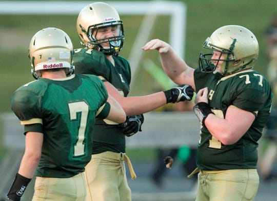 Pete Cender (center) is congratulated by teammates Cody Wiggins (left) and Cameron Englund after scoring a touchdown for Howell in a 2011 football game.