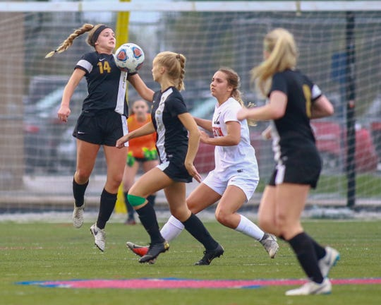Howell's Lydia Johnson (14) jumps in an effort to control the soccer ball in a 5-0 loss to Brighton on Thursday, May 2, 2019.